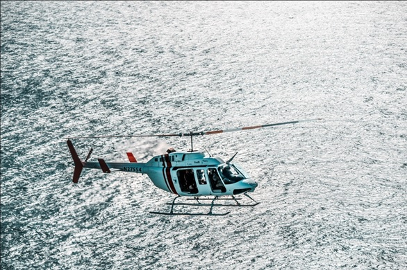 helicopter flying over ocean image