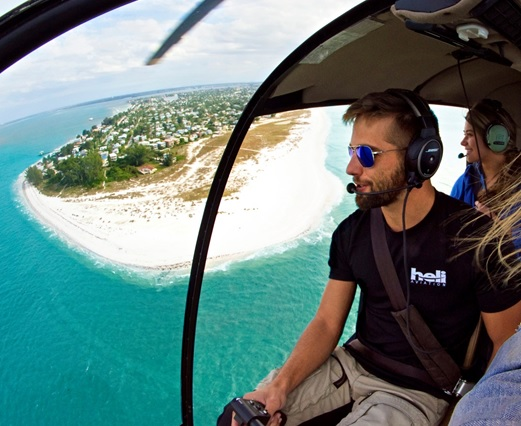 A pilot flying a helicopter beach tour in Florida.