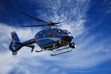 A blue helicopter in the sky