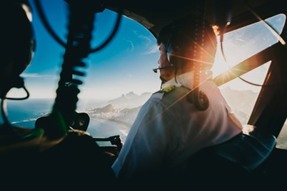 A helicopter pilot flying across the sea