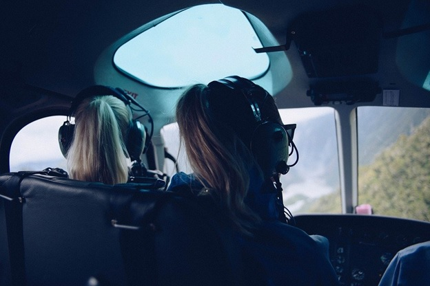 Two girls sitting in a helicopter and enjoying the view