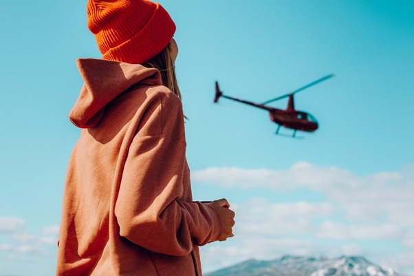 A girl watching a helicopter in the air