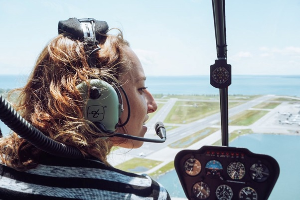 A woman taking a helicopter tour and wearing a headset