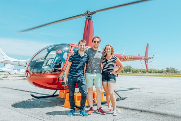 Three friends standing in front of a helicopter